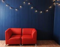 Rotes ledernes Sofa auf einem Hintergrund der blauen Wand mit Retro- Girlande von Glühlampen Beschaffenheit für den Entwurf Lizenzfreies Stockbild