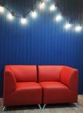 Rotes ledernes Sofa auf einem Hintergrund der blauen Wand mit Retro- Girlande von Glühlampen Beschaffenheit für den Entwurf Stockbild
