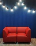 Rotes ledernes Sofa auf einem Hintergrund der blauen Wand mit Retro- Girlande von Glühlampen Beschaffenheit für den Entwurf Stockfotos