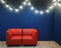 Rotes ledernes Sofa auf einem Hintergrund der blauen Wand mit Retro- Girlande von Glühlampen Beschaffenheit für den Entwurf Lizenzfreie Stockbilder
