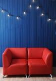 Rotes ledernes Sofa auf einem Hintergrund der blauen Wand mit Retro- Girlande von Glühlampen Beschaffenheit für den Entwurf Lizenzfreie Stockfotos