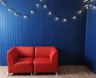 Rotes ledernes Sofa auf einem Hintergrund der blauen Wand mit Retro- Girlande von Glühlampen Beschaffenheit für den Entwurf Lizenzfreies Stockfoto
