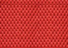 Rotes Lederpolster mit vielen Löchern Stockfotografie