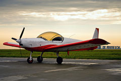 Rotes Leichtflugzeug im Sonnenaufganglicht Stockbilder