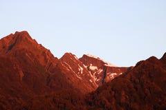 Rotes Licht bei Sonnenuntergang auf Bergen Franz Josef, NZ Lizenzfreies Stockbild