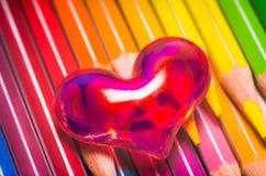 Rotes lichtdurchlässiges Herz auf farbigen Bleistiften Stockfotos