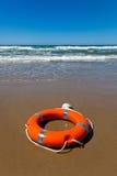 Rotes lifebuoy Lügen auf dem Sand auf dem Strand Lizenzfreies Stockbild