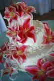 Rotes lilie bedeckte Hochzeitstorte Stockfoto