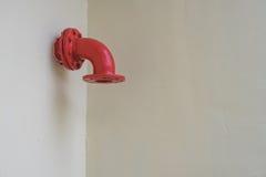 Rotes Metallrohr auf der weißen Wand Stockbild