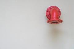 Rotes Metallrohr auf der weißen Wand Lizenzfreies Stockbild