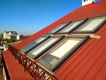 Rotes mit Ziegeln gedecktes Hausdach mit Dachbodenfenstern ?berdachung des Baus, Fensterinstallation, modernes Architekturkonzept stockfotografie
