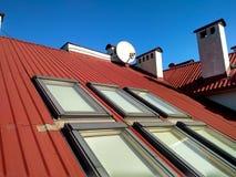 Rotes mit Ziegeln gedecktes Hausdach mit Dachbodenfenstern ?berdachung des Baus, Fensterinstallation, modernes Architekturkonzept stockbild