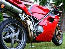 Rotes Motorrad Ducati 996s in einem Garten Lizenzfreie Stockfotos