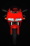 Rotes Motorrad gegen schwarzen Hintergrund Lizenzfreie Stockfotos