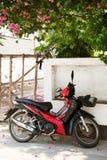 Rotes Motorrad parkte unter einem schönen blühenden Baum Lizenzfreies Stockfoto