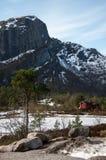 Rotes norwegisches Holzhaus im Winterwald nah an dem mou Lizenzfreie Stockfotos