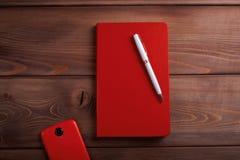 Rotes Notizbuch und ein Smartphone auf dunklem hölzernem Hintergrund Stockfoto