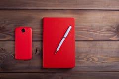 Rotes Notizbuch und ein Smartphone auf dunklem hölzernem Hintergrund Lizenzfreie Stockfotos