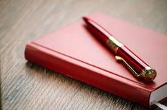 Rotes Notizbuch und roter fantastischer Stift auf dem Tisch Lizenzfreies Stockfoto