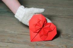 Rotes Origamiherz auf hölzernem Hintergrund Stockfoto