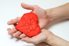 Rotes Origamiherz in Männer ` s Händen Lizenzfreie Stockfotos