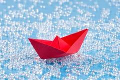 Rotes Origamipapierschiff auf blauem Wasser mögen Hintergrund stockfotos