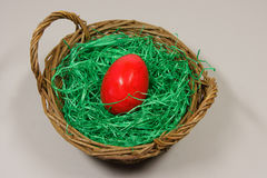 Rotes Osterei in einem Korb Lizenzfreie Stockfotos