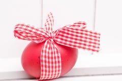 Rotes Osterei mit Farbband Stockfoto