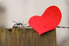 Rotes Papier der Weinlese formte Herz mit Metalldraht und hölzernem Beitrag Stockfotografie