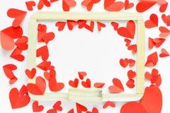 Rotes Papier formte Herz um whiteboard auf Weiß lokalisiertem backg Stockfoto