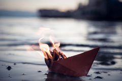 Rotes Papierboot auf Feuer Stockbilder