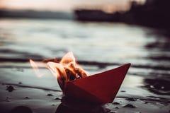 Rotes Papierboot auf Feuer Lizenzfreie Stockbilder
