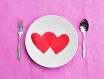 Rotes Papierherz auf dem weißen Teller-, Liebes- und Valentinstagkonzept Stockfoto