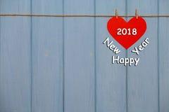 Rotes Papierherz mit einem 2018-guten Rutsch ins Neue Jahr-Text auf blauem hölzernem Hintergrund Stockbilder