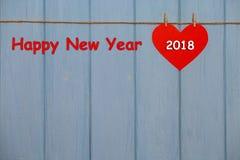Rotes Papierherz mit einem 2018-guten Rutsch ins Neue Jahr-Text auf blauem hölzernem Hintergrund Stockbild