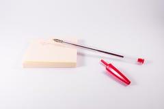 Rotes Pen Ink Writing Sticky Note-Notizblock-Anzeigen-Gekritzel-Weiß Stockfotografie