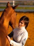 Rotes Pferd mit seinem Mitfahrer Stockbild