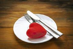 Rotes Plüsch-Herz mit Gabel und Messer, in beendet der Mahlzeit-Position auf einer weißen Platte Hölzerner Hintergrund Unbedeuten stockbild