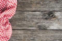 Rotes Plaidküchengewebe auf altem hölzernem Hintergrund stockfotos