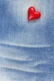 Rotes Plastikherz auf Blue Jeans-Beschaffenheit Lizenzfreies Stockbild