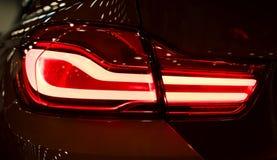 Rotes Rücklicht auf einem modernen Auto mit Reflexion Das Nahaufnahme-zurück rote Rücklichtauto Stockfoto