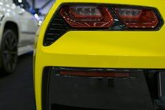 Rotes Rücklicht auf einem modernen gelben Auto mit Reflexion Das Nahaufnahme-zurück rote Rücklichtauto Stockbilder