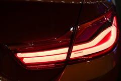 Rotes Rücklicht auf einem modernen roten Auto mit Reflexion Die Nahaufnahme Stockfoto