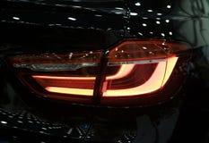 Rotes Rücklicht auf einem modernen schwarzen Auto mit Reflexion Das Nahaufnahme-zurück rote Rücklichtauto Lizenzfreie Stockfotos