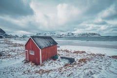 Rotes rorbu Haus verschüttete auf Strand von Fjord, Norwegen stockfoto