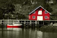Rotes Rorbu und Boot beim Lofoten Stockfoto
