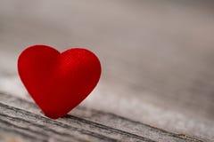 Rotes Satinherz auf hölzernem Hintergrund-, Valentinsgruß- oder Muttertageshintergrund, Liebesfeiern Stockfoto