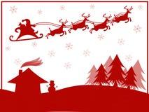 Rotes Schattenbild von Santa Claus mit dem Ren, das über Dorf fliegt Stockfotos