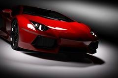 Rotes schnelles Sportauto im Scheinwerfer, schwarzer Hintergrund Glänzend, neu, luxuriös Stockbild