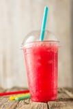 Rotes Slushie-Getränk in der Plastikschale mit Strohen Stockbild